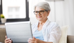 technology, old age and people concept - happy senior woman in glasses with laptop computer at home